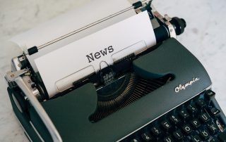 A typewriter with a piece of paper that says News coming out of it.