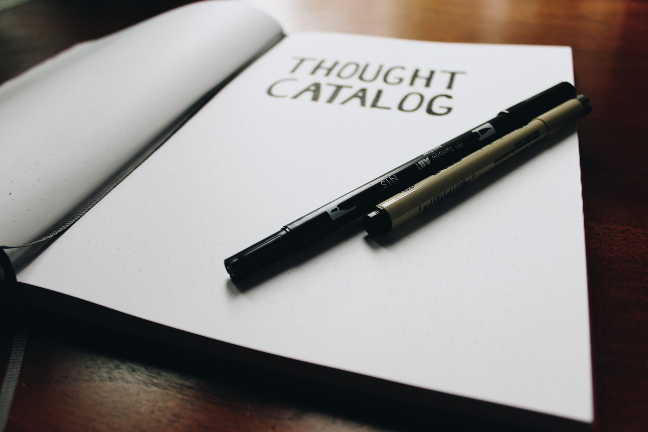 A notebook open on a table with the word 'though catalog' on. Two pens sit on top of the page.