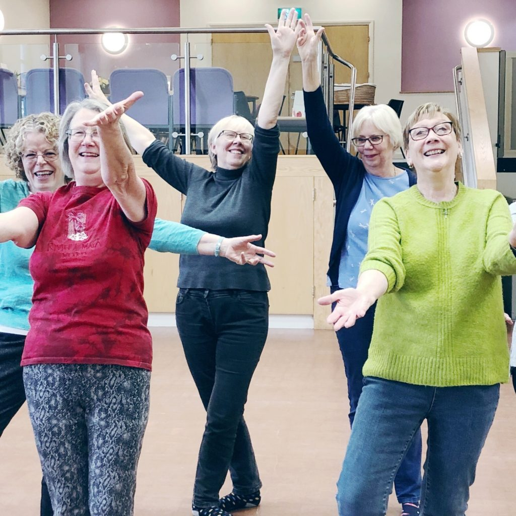 A group of people together holding a pose - they are all smiling with their arms stretched out wide in different directions.