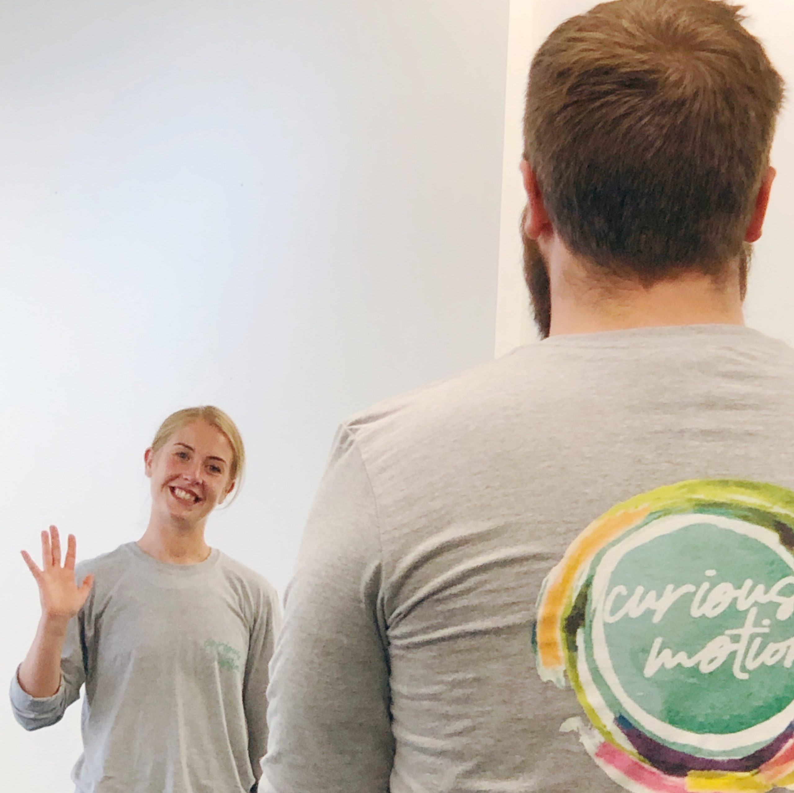 Two people - one person has their back to the camera and the Curious Motion logo can be seen on their t-shirt. In the background is another person facing the camera, waving and smiling.