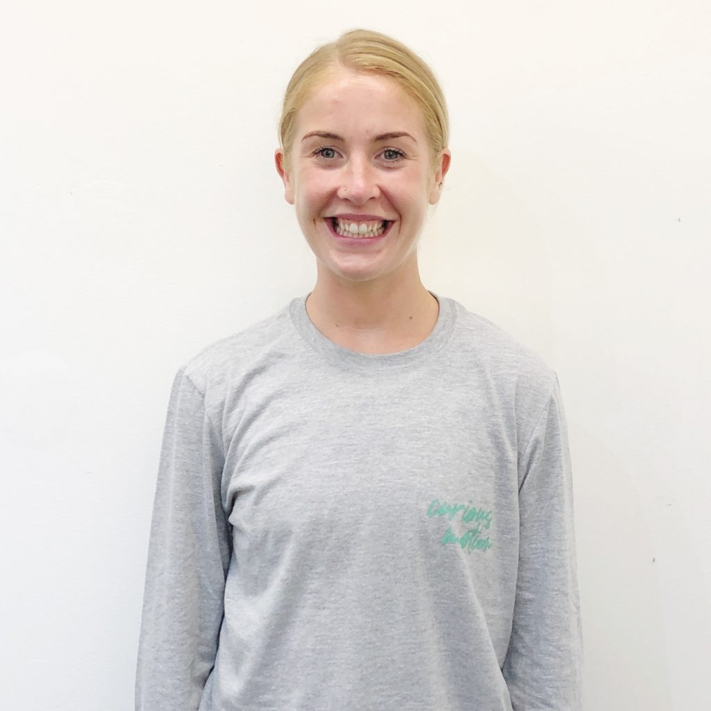 Jess facing the camera and smiling on a white background. She is wearing a grey top with the words Curious Motion on it in green.