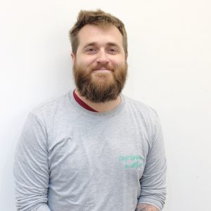 Matt facing the camera and smiling on a white background. He is wearing a grey top with the words Curious Motion on it in green.