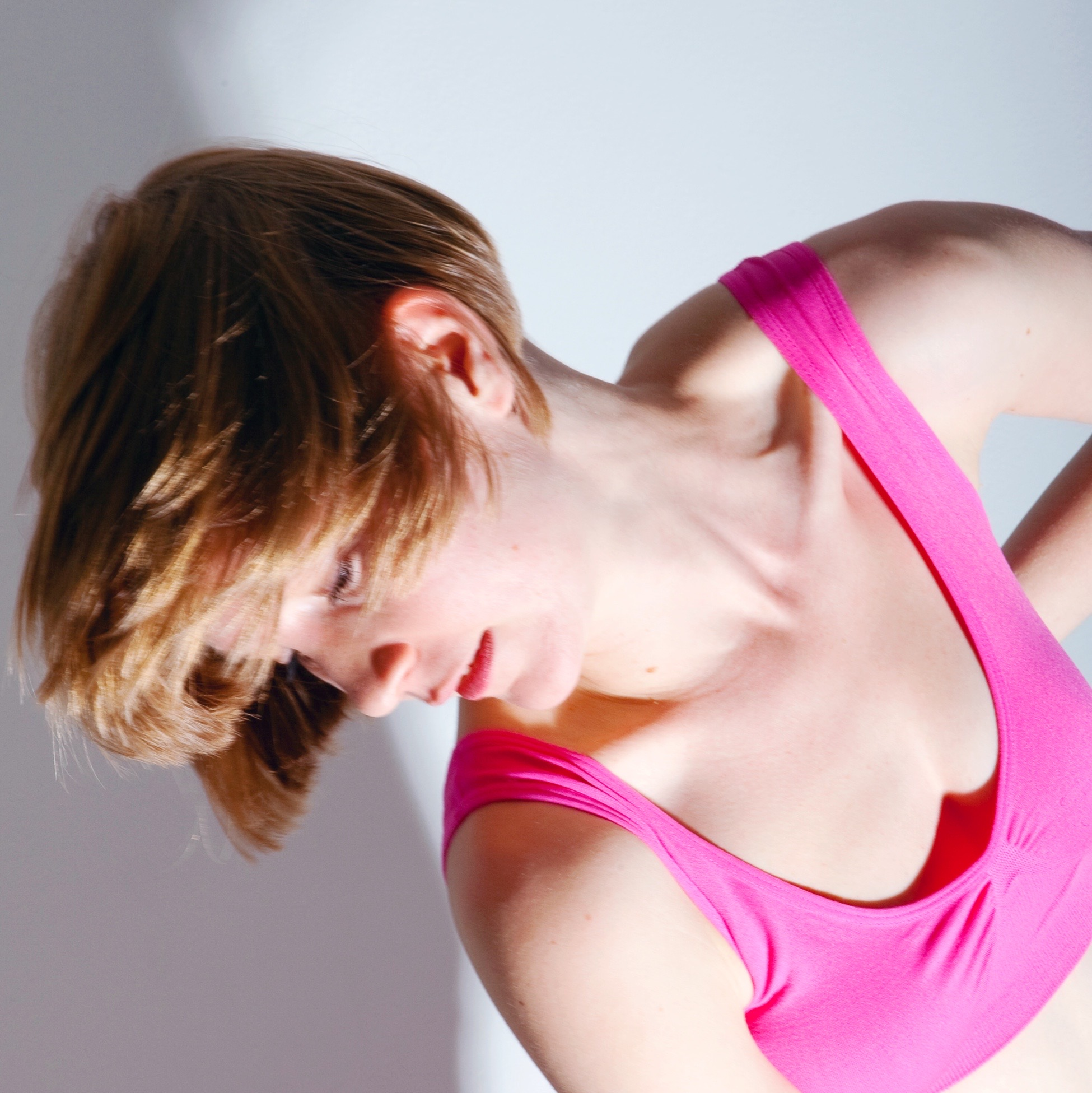 Photo of a dancer leaning to left hand side of the image, wearing a bright pink crop top.