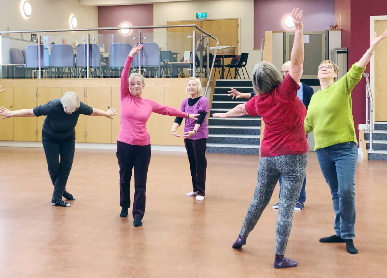 A group photo of Brews & Grooves participants. They are in a church hall and all standing in different dance poses. The person in the middle is facing the camera and everyone else is around her facing different directions.