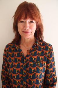 A photo of Trizia - she is a white female, with shoulder length red/brown hair. She's wearing a printed shirt with animals on and is smiling at the camera.