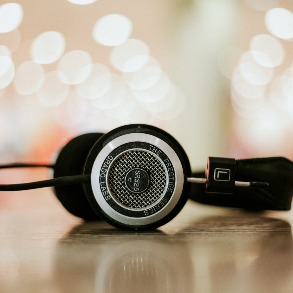 Large headphones lying on a surface. Blurred lights in the background